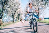 Eine fröhliche Frau auf dem Fahrrad