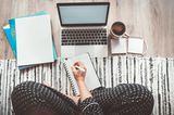 Eine Frau mit Tagesplan am Laptop