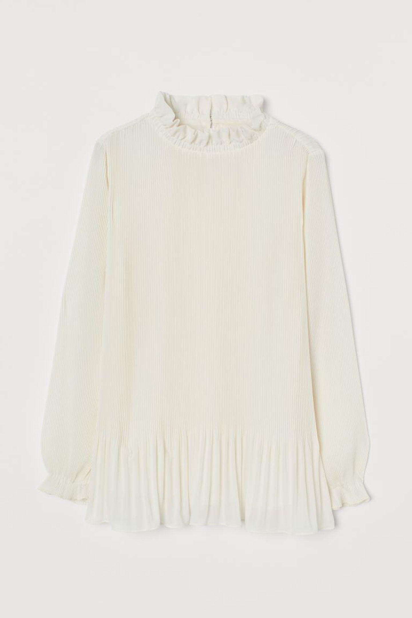 Eine leichte Bluse ist nicht nur super angenehm zu tragen, sie verleihtjedem Look auch diesen Hauch von Glamour. Die sanften Plisséefalten und süßen Rüschen an Kragen und Ärmeln machen sie zudem zum echten Hingucker-Piece. Von H&M, um 30 Euro.