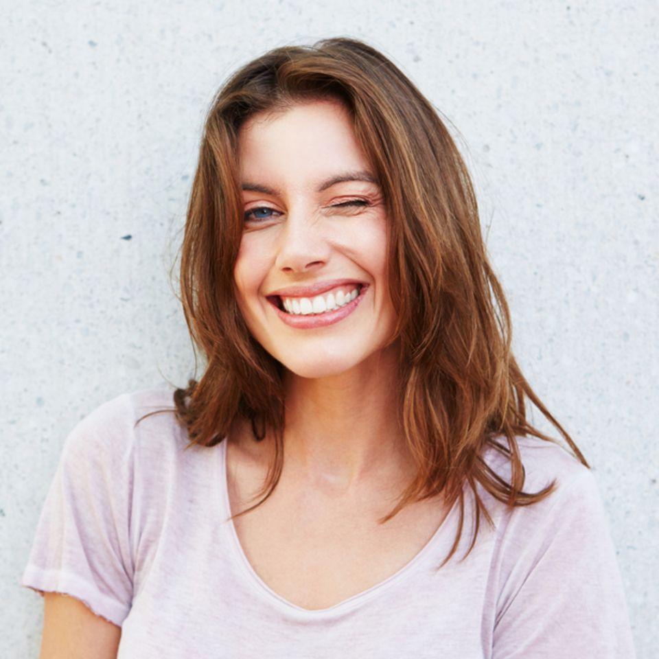 Brüchige Haare: Lächelnde Frau mit hellbraunen Haaren.