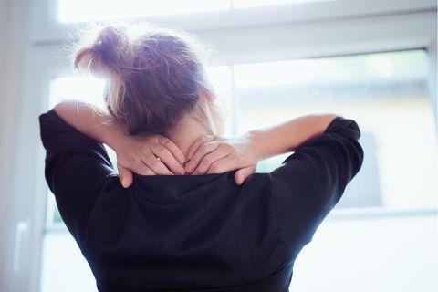 Frau massiert sich Rücken
