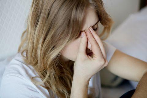 Nasennebenhöhlenentzündung Hausmittel: Frau fasst sich an die nase