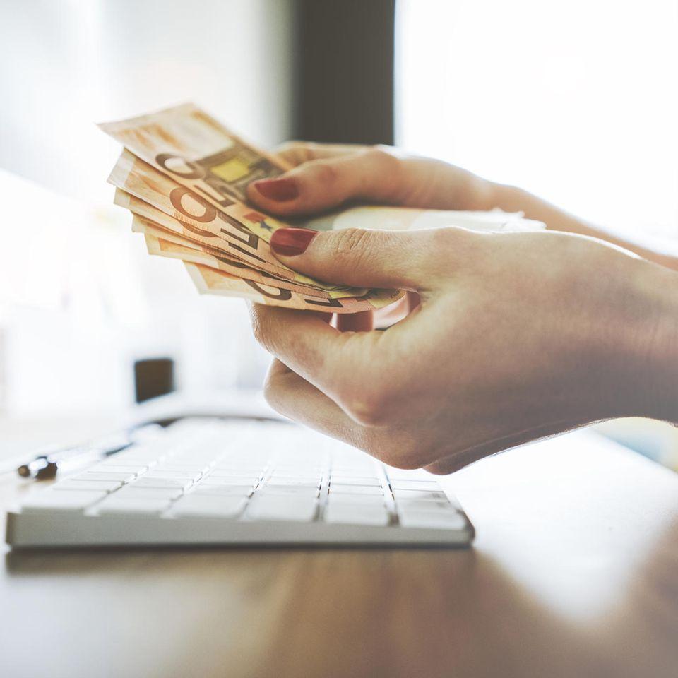Kakeibo: Frau mit Geldscheinen in der Hand