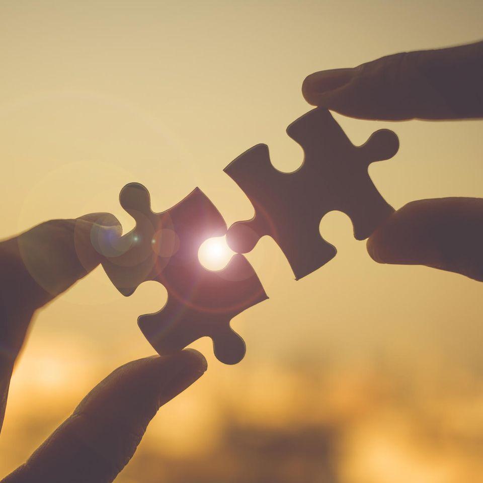 Beziehungsziele: Zwei Hände fügen Puzzleteile aneinander
