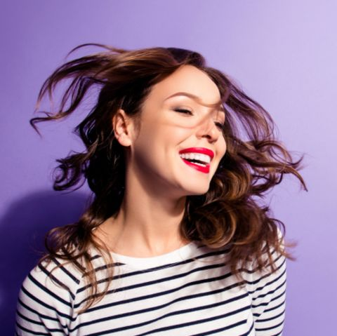 Schnell fettende Haare: Frau mit wehenden braunen Haaren.