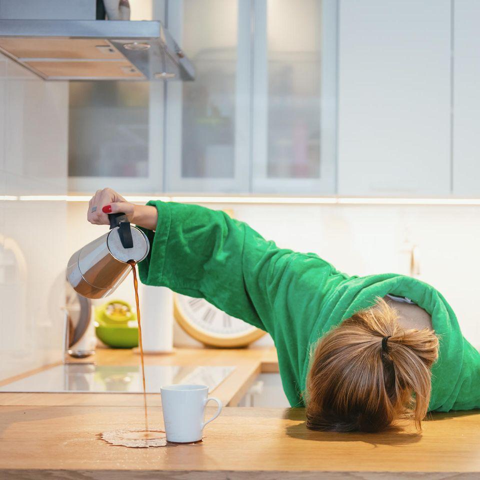Frau gießt Kaffee neben die Kanne