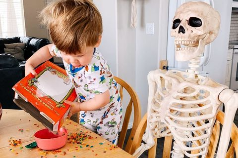 Zweijähriger und Skelett sind beste Freunde