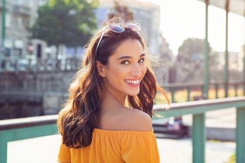 Fettige Haare: Lächelnde Frau mit brünetten Haaren.