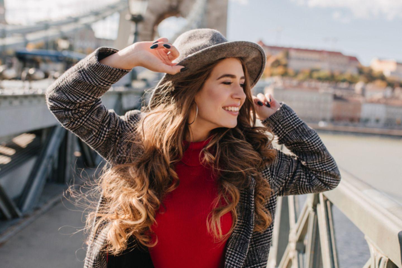Dicke Haare: Frau mit langen Wellen und Hut