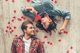 Ein Paar liegt auf dem Boden umgeben von Herzen
