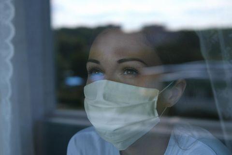 Corona aktuell: Frau mit Maske am Fenster