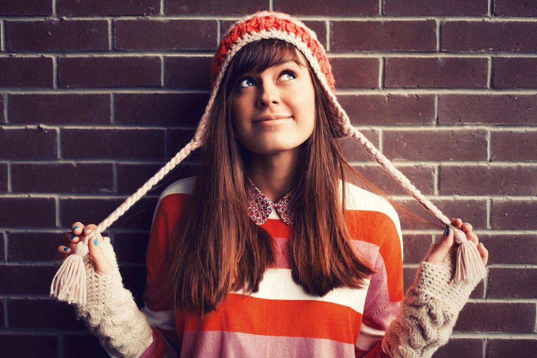 Horoskop: Eine fröhliche Frau mit Mütze und Pulli