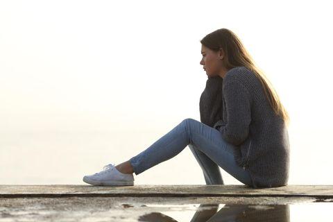 Macht der Gewohnheit: Eine traurige Frau sitzt auf einer Mauer