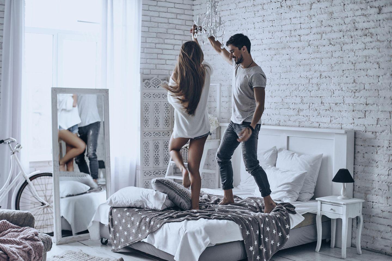 Corona aktuell: Ein Paar tanzt auf dem Bett