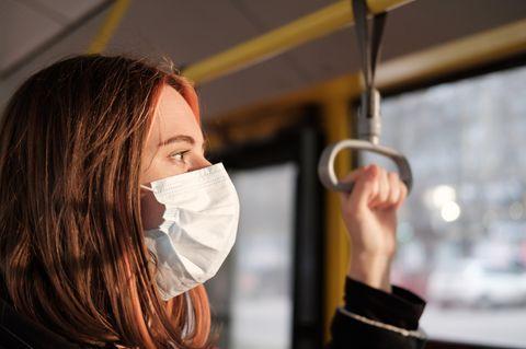 Corona aktuell: Frau mit Mundschutz im Bus