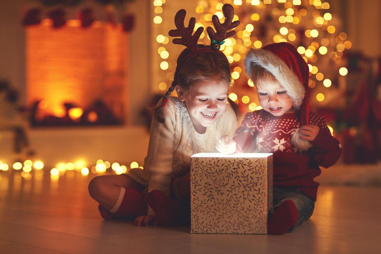 Weihnachten mit Kindern: Zwei Kinder packen Geschenk aus