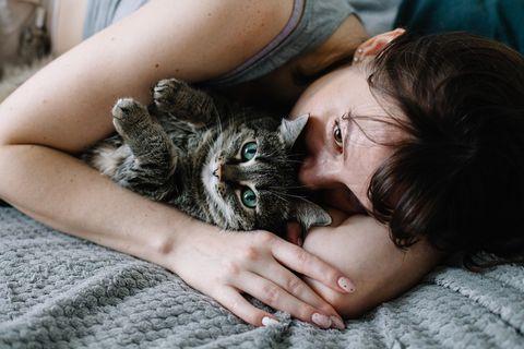 Verletzte Gefühle: Frau liegt mit Katze im Bett