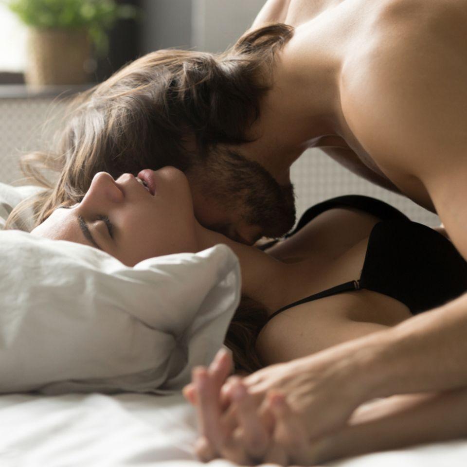 Hals küssen: Pärchen liegt auf dem Bett
