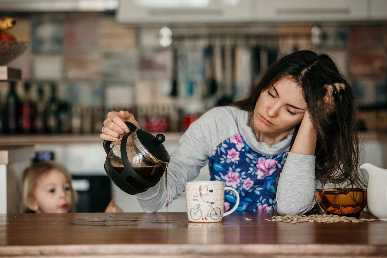 Schlafentzug: Erschöpfte Frau gießt Kaffee ein