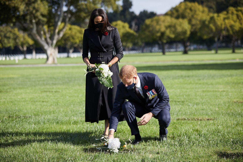 """Für den Besuch des """"National Cemetery"""" in Los Angeles wählt Herzogin Meghan einen schwarzen Mantel von Brandon Maxwell. Dazu kombiniert sie spitze Pumps mit Riemchen vonJennifer Chamandi und eine schwarze Clutch. Ein Taillengürtel betont gekonnt die Körpermitte der ehemaligen Schauspielerin - und das nur wenige Tage nachdem Schwangerschaftsgerüchte laut wurden!Gemeinsam mit Prinz Harry legt sie dort am """"Remembrance Day"""" in Gedenken an die gefallenen Soldaten einen handgepflückten Blumenstrauß nieder. Masken dürfen in Zeiten der Coronapandemie natürlich auch nicht fehlen!"""