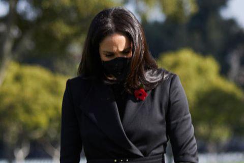 """Für den Besuch des """"National Cemetery"""" in Los Angeles wählt Herzogin Meghan einen schwarzen Mantel von Brandon Maxwell. Dazu kombiniert sie spitze Pumps mit Riemchen vonJennifer Chamandi und eine schwarze Clutch. Ein Taillengürtel betont gekonnt die Körpermitte der ehemaligen Schauspielerin - und das nur wenige Tage nachdem Schwangerschaftsgerüchte laut wurden!Gemeinsam mit Prinz Harry legt sie in Gedenken an die gefallenen Soldaten einen handgepflückten Blumenstrauß nieder. Masken dürfen in Zeiten der Coronapandemie natürlich auch nicht fehlen!"""