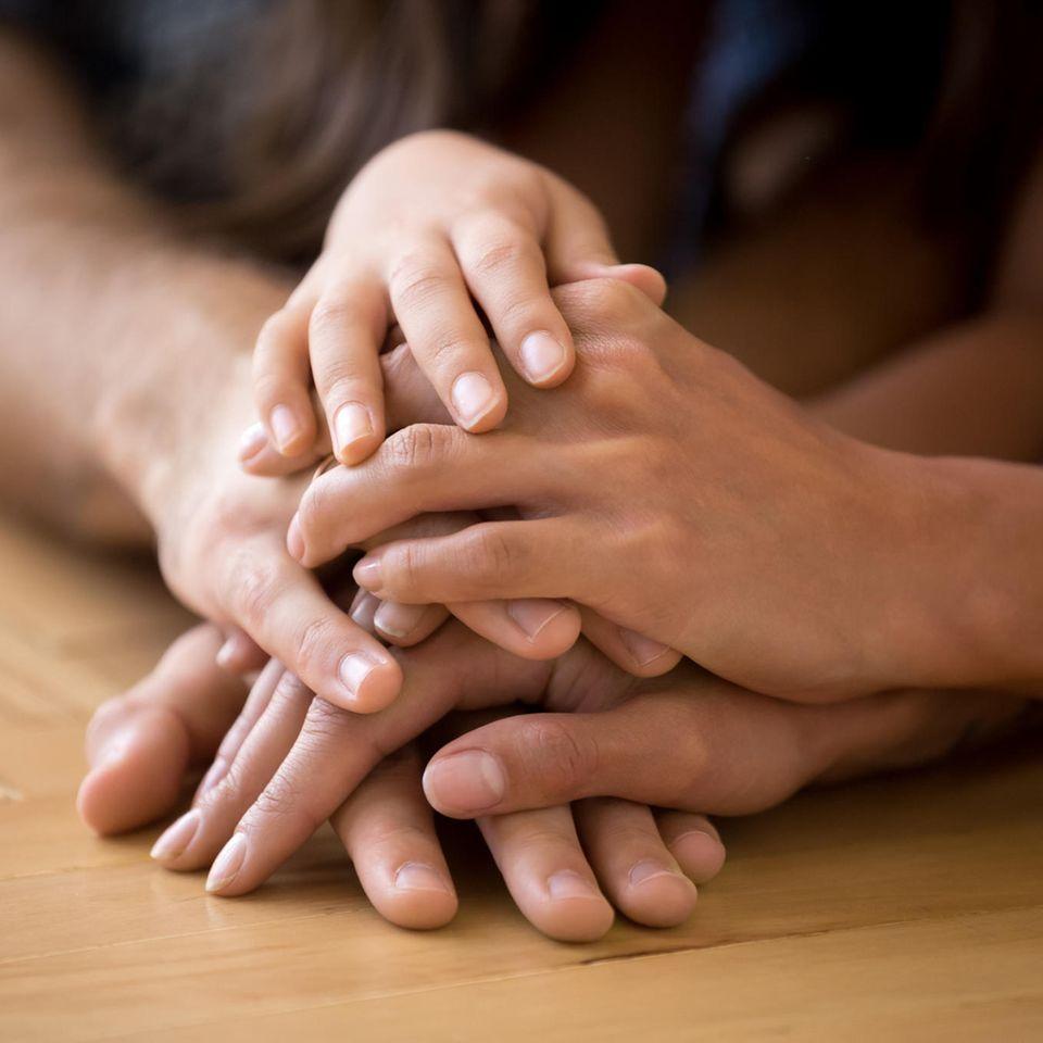 Alleinstehende Adoption: Kinderhände auf Erwachsenenhand