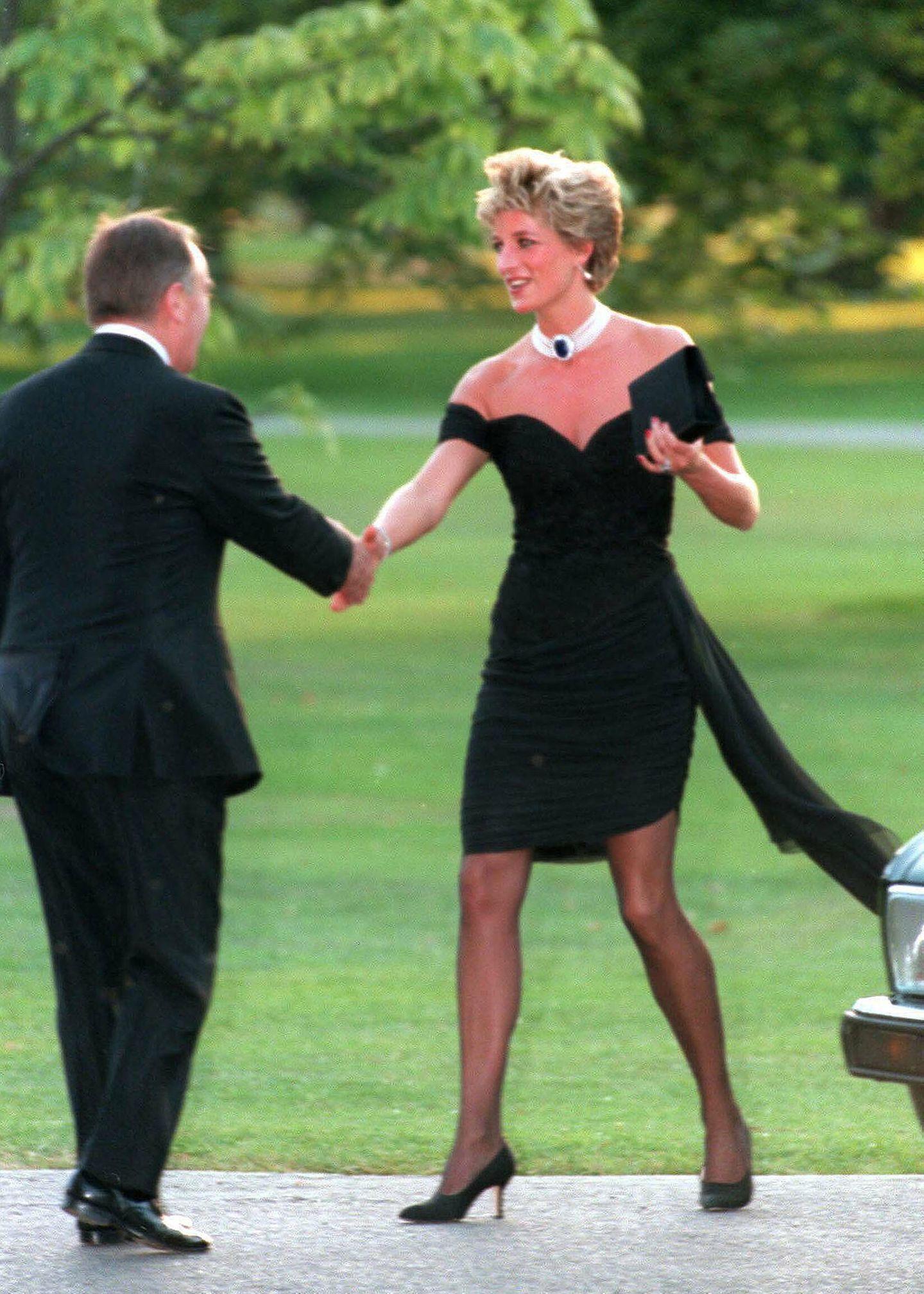 """Es ist das vermutlich berühmteste Kleid der Welt – das sogenannte """"Rache-Kleid""""! Bei einer Sommerparty 1994 hebte Diana das kleine Schwarze auf ein neues Style-Level. Der enge Schnitt und die nackten Schultern waren ultrasexy und sorgten für einen Auftritt, der wohl für immer unvergessen bleibt. Das LBD wurde übrigens """"Rache-Kleid"""" getauft, weil Prince Charles nur wenige Stunden vor Dianas Auftritt in einem TV-Interview öffentlich zugab, während seiner Ehe mit ihreine Affäre mit Camilla Parker-Bowles gehabt zu haben. Kein Wunder also, dass Diana der Welt danach nur zu gerne gezeigt hat, was ihr untreuer Exmann da verpasst, oder?"""