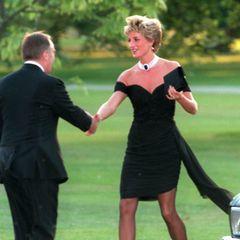 """Es ist das vermutlich berühmteste Kleid der Welt – das sogenannte """"Rache-Kleid""""! Bei einer Sommerparty 1994 hob Diana das kleine Schwarze auf ein neues Style-Level. Der enge Schnitt und die nackten Schultern waren ultrasexy und sorgten für einen Auftritt, der wohl für immer unvergessen bleibt. Das LBD wurde übrigens """"Rache-Kleid"""" getauft, weil Prince Charles nur wenige Stunden vor Dianas Auftritt in einem TV-Interview öffentlich zugab, während seiner Ehe mit ihreine Affäre mit Camilla Parker-Bowles gehabt zu haben. Kein Wunder also, dass Diana der Welt danach nur zu gerne gezeigt hat, was ihr untreuer Exmann da verpasst, oder?"""