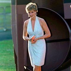 """Einmal aus dem royalen Käfig ausgebrochen, gab es vor allem modisch für Diana kein Halten mehr. Für dasselbe Sommerfest, aber ein Jahr später, setzte die damals 34-Jährige diesmal auf """"das kleine Weiße"""", aber wieder auf einen engen Schnitt und tiefen Ausschnitt. Tausende Pailletten sorgten zudem dafür, dass Diana auch diesmal wieder der Mittelpunkt der Party war."""