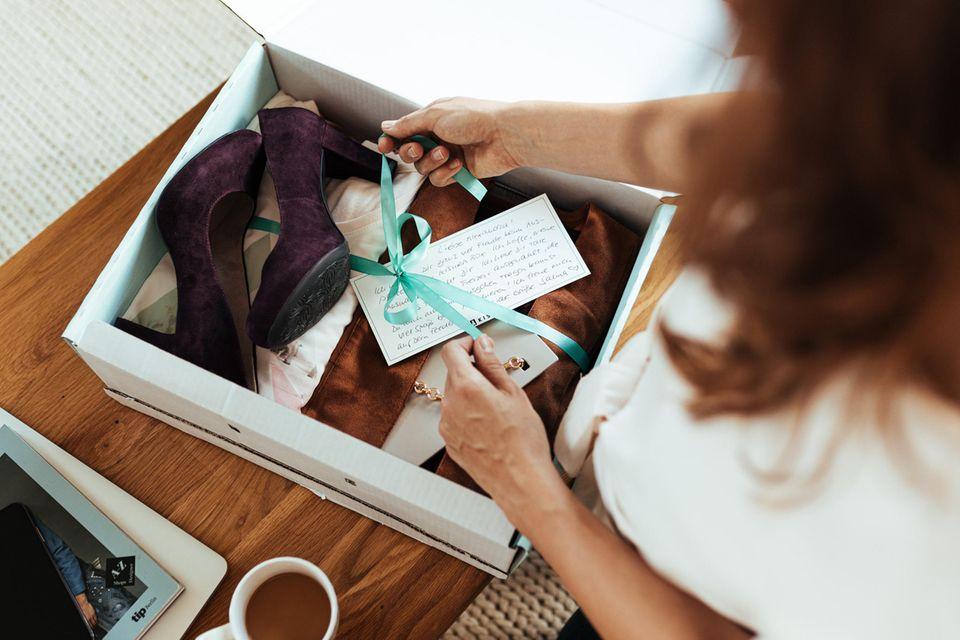 Frau öffnet Kisura-Box mit individueller Kleidung