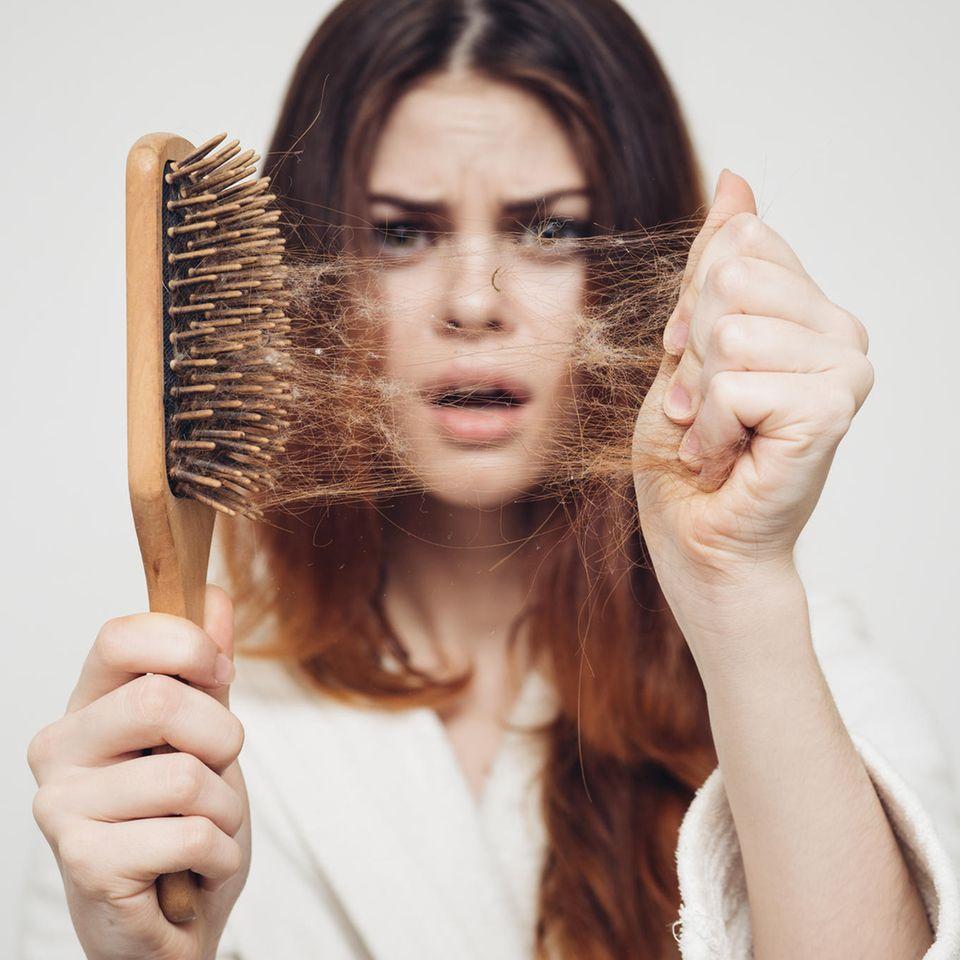 Frau zieht Haare aus einer Bürste