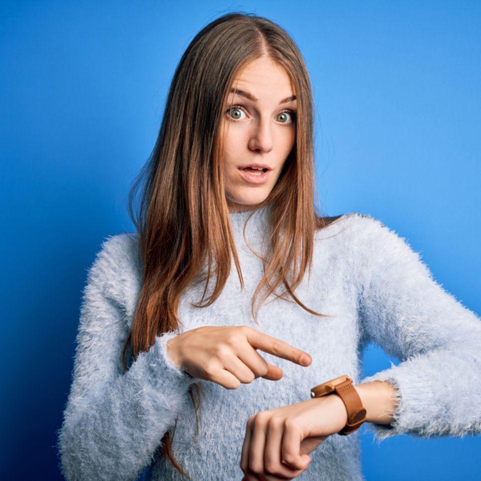 Ungeduld: Frau zeigt auf eine Uhr am Handgelenk.