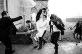 Die schönsten Hochzeitsbilder des Jahres: Bräutigam trägt Braut im Regen