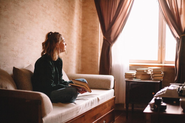 Corona aktuell: Nachdenkliche junge Frau auf dem Sofa