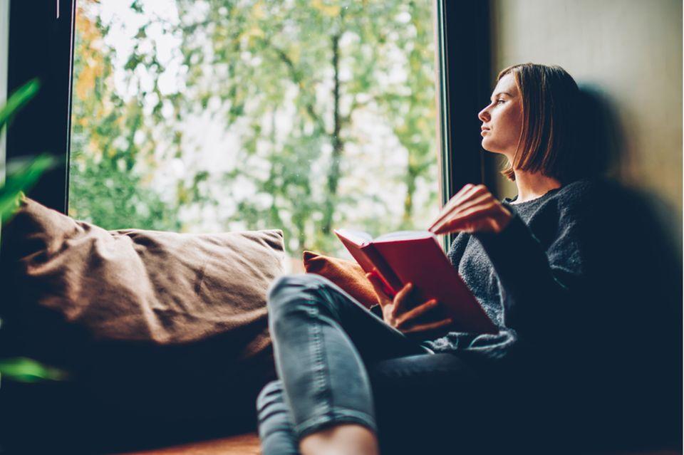 Bücher zum Nachdenken: Frau sitzt mit Buch auf der Fensterbank