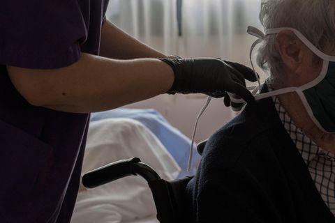 Corona aktuell: Eine Pflegerin hilft einer Seniorin mit dem Mundschutz