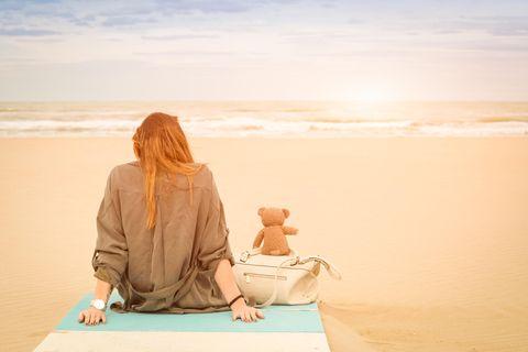Whisper: Eine Frau sitzt am Strand mit einem Teddy