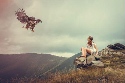 Krafttiere: Frau sitzt auf einem Berg und ein Adler fliegt auf sie zu
