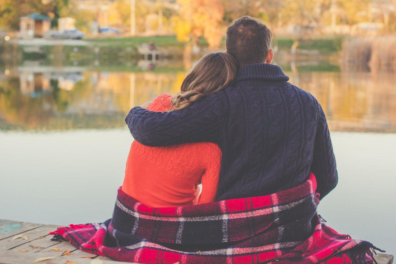 Studie: Ein Pärchen sitzt mit einer Decke Arm in Arm am See