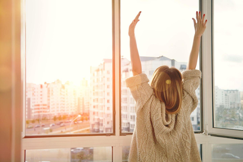 Selfcare: Eine Frau streckt sich am Fenster