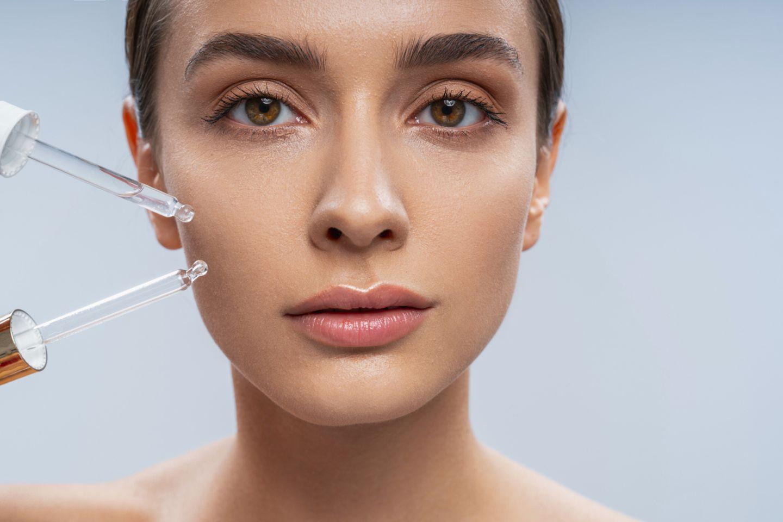 Junge Frau mit straffer Haut trägt Gesichtsöl auf