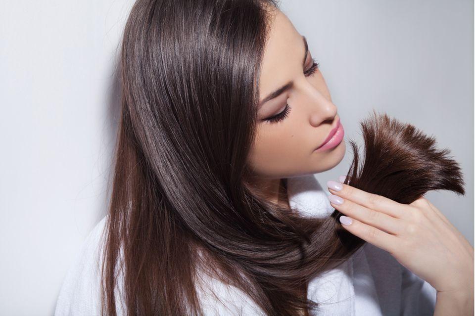 Von Blond auf Braun: Frau mit braunen Haaren hält eine Strähne in den Fingern.