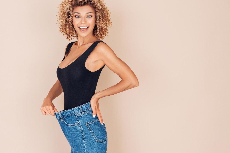Frau zeigt Gewichtsverlust an zu weiter Jeans