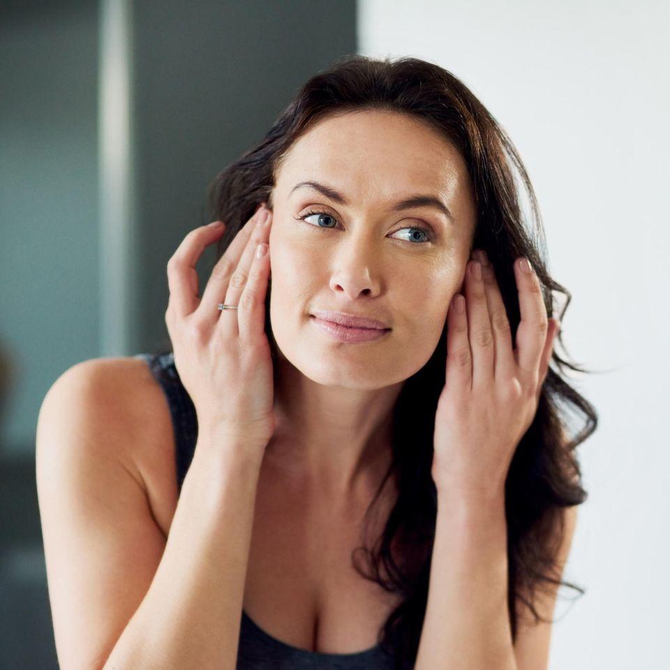 Frau betrachtet straffe Haut im Spiegelbild