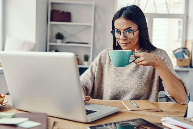 Home-Office-Tipps: Frau sitzt am Schreibtisch und hält Kaffeetasse in der Hand.