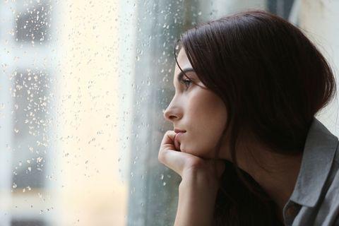 Corona aktuell: Traurige Frau sieht aus dem Fenster