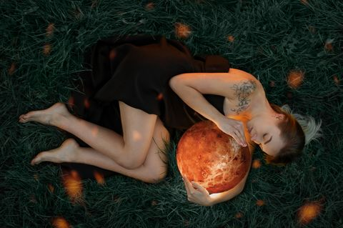 Venus Zeichen: Frau liegt auf der Erde und hält leuchtende Kugel in den Händen.
