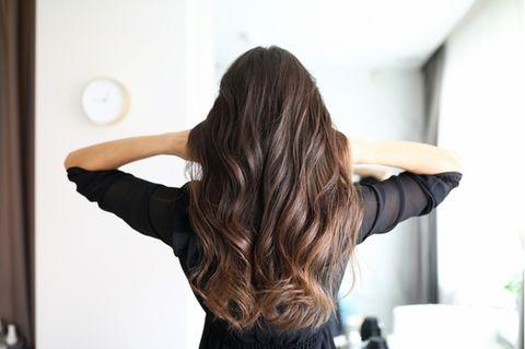 Haarwachstum anregen: Frau von hinten mit langen gewellten Haaren.