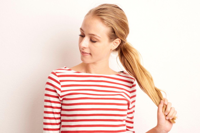 Haare stärken: Frau zieht an ihren blonden langen Haaren.