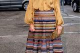Ein Outfit, dassofort gute Laune versprüht: Königin Máxima wird nicht umsonst als royaler Sonnenschein benannt, denn sie sorgt selbst an einem dunklen November-Tag mit hellen, glänzenden und bunten Farben für einen Eye-Catcher-Look. Der Glockenrock ist von der österreichischen Designerin Lena Hoschek. InKombination mit einer senffarbenen Seidenbluse kommt er besonders gut zur Geltung. Merke: Gerade Satin oder Seide reflektierenLicht einmal mehr und sorgt für den Wow-Effekt im Winter. Farblich abgestimmte Pumps aus Wildleder vervollständigen das Erscheinungsbild.
